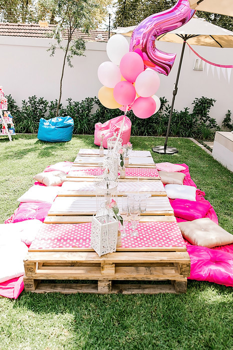 Rustic outdoor pallet setup with matching cushions and runners for hire.