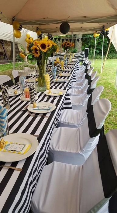 Black catering chairs for adults with theme matching chair covers and tiebacks.