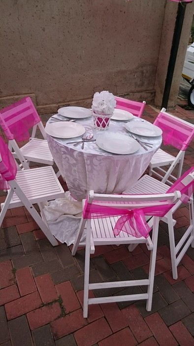 Small round tables and white chairs to hire.