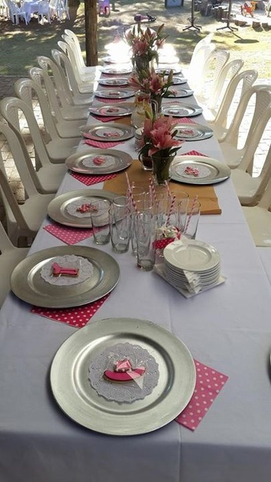 White catering chairs with no chair covers and trestle tables with white table cloths for a kitchen tea party.
